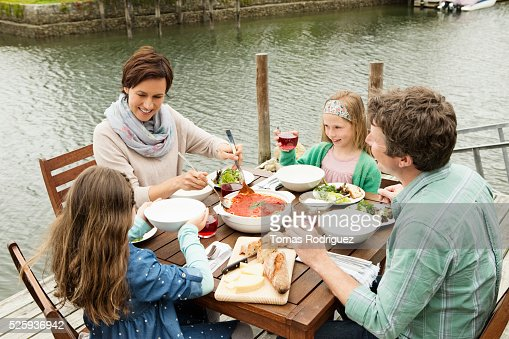 Portrait of parents and girls (6-7), (8-9) eating outdoors : Photo