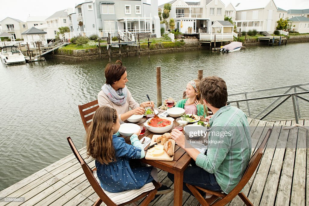 Portrait of parents and girls (6-7), (8-9) eating outdoors : Stock Photo