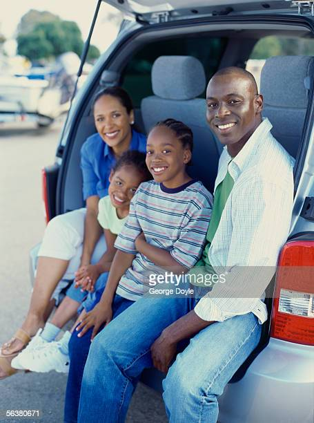 portrait of parents and their children sitting at the back of a car