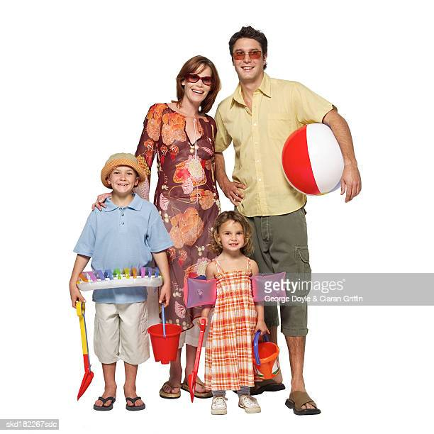 Portrait of parents and two children (4-9) holding bucket and spade