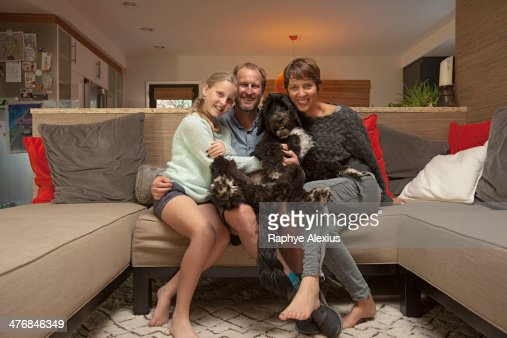 Portrait of parents, daughter and pet dog on sofa : Stock Photo