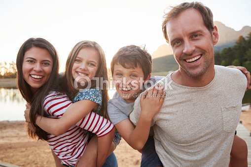 Portrait Of Parents Giving Children Piggyback Ride In Countryside : Stock Photo
