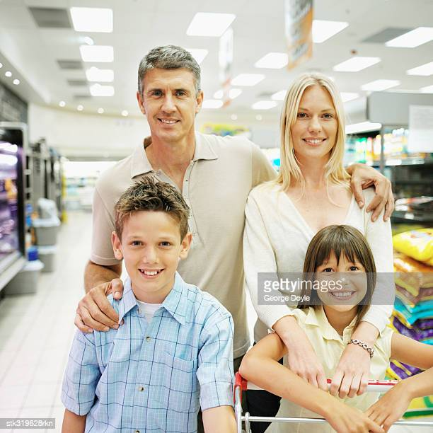 portrait of parents with their son and daughter in a supermarket