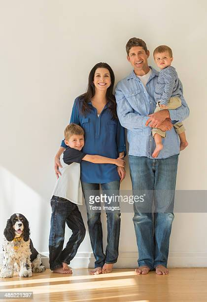 Portrait of parents with two sons (12-17 months, 6-7) and dog