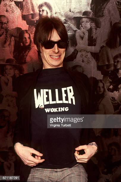 Portrait of Paul Weller of The Jam wearing a sweatshirt with the slogan 'Weller Woking' United Kingdom 1982