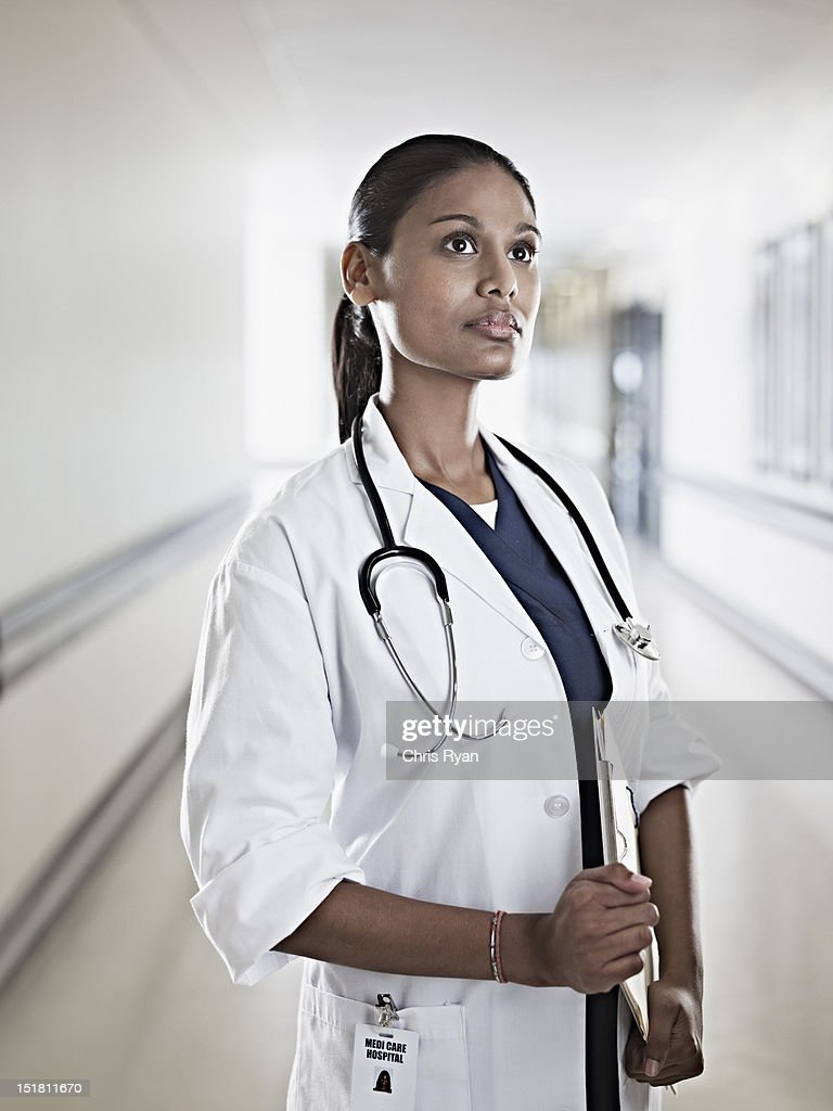 Portrait of pensive doctor holding medical record in hospital corridor : Stock Photo