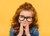 portrait of pensive little kid in eyeglasses isolated on yellow