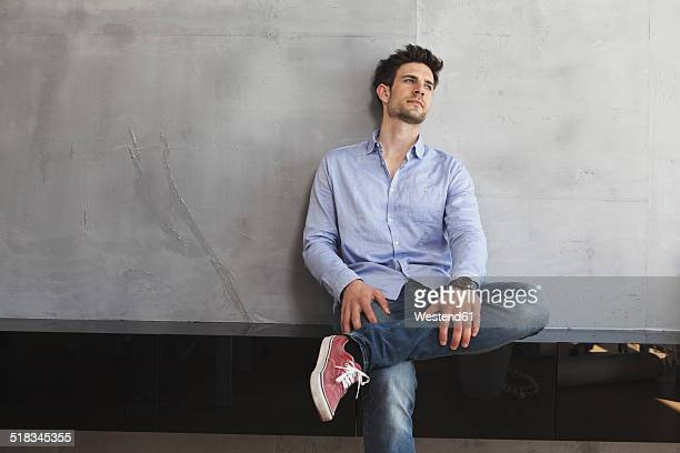 Portrait of pensive man leaning on wall