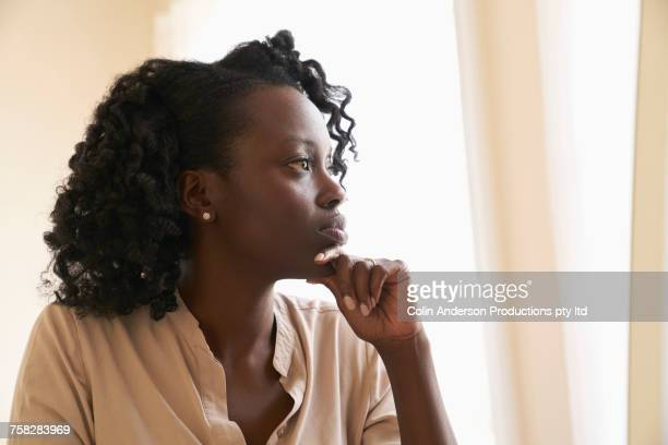 Portrait of pensive woman near window
