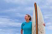 Portrait of pensive woman with surfboard