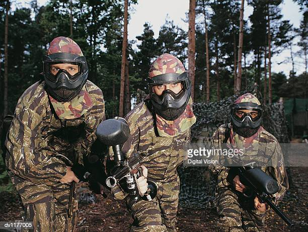 Portrait of People Paintballing Dressed in Camouflage Clothing and Wearing Face Masks