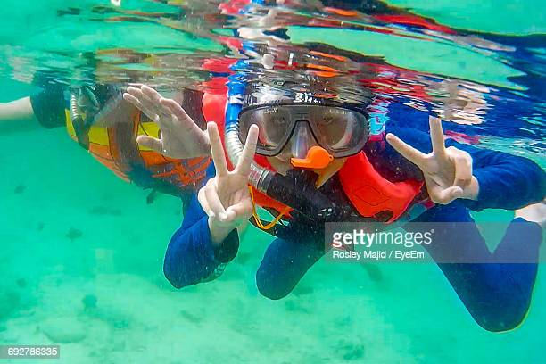 Portrait Of Person Showing Peace Sign While Snorkeling In Sea
