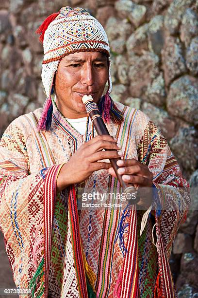 Portrait of Peruvian man playing a flute, Inca ruins, Pisac