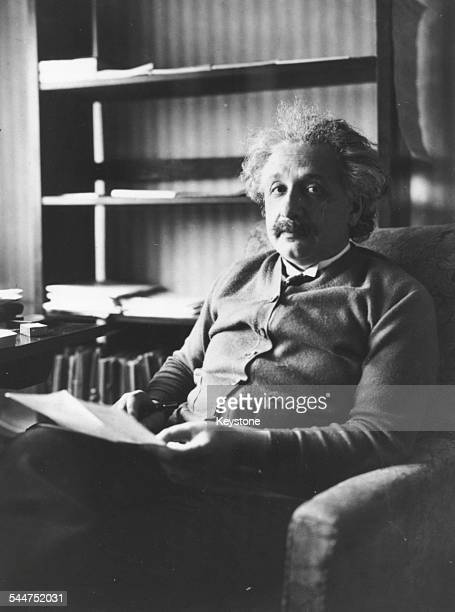 Portrait of physicist Albert Einstein sitting in an armchair and reading 1929