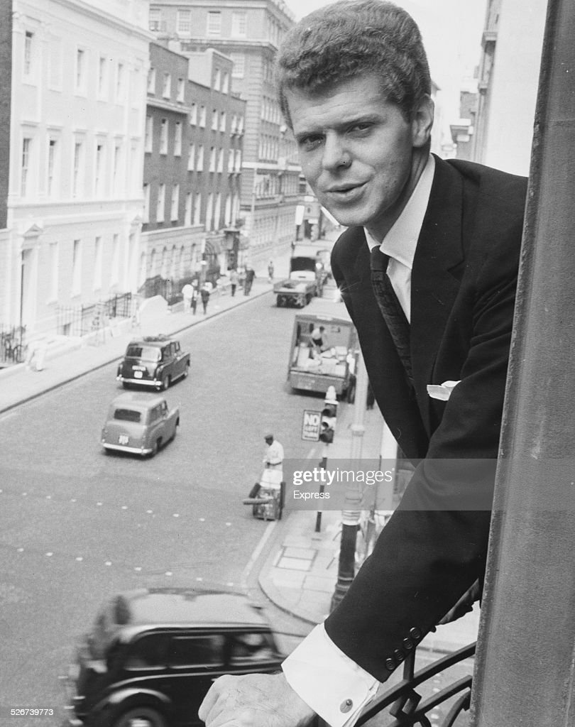 Portrait of pianist Van Cliburn leaning from the window of his room at Claridge's Hotel in London to play at London Symphony Orchestra gala concert...