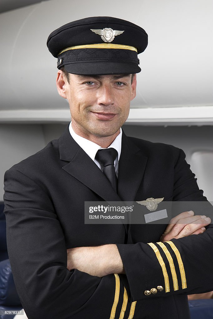 Portrait of pilot standing in aisle of airplane : Stock Photo