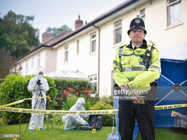 Portrait of policeman at crime scene, forensic scientists outside house in background