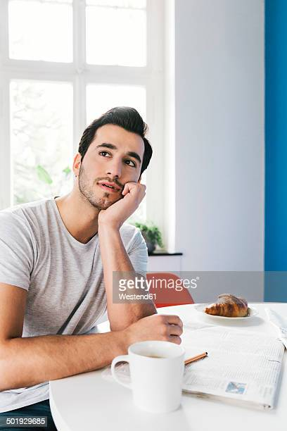 Portrait of pondering young man sitting at breakfast table with newspaper