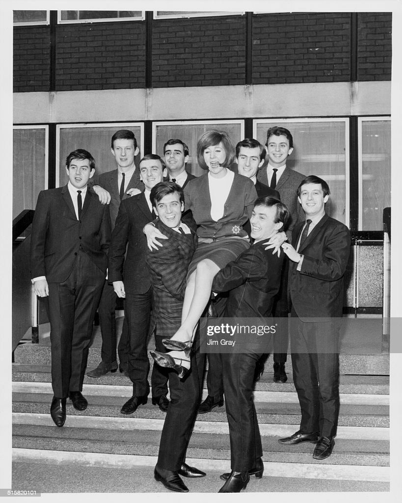 Portrait of pop stars (L-R) Billy J Kramer, Cilla Black and Gerry Marsden, standing in from of the rest of the band 'Gerry and the Pacemakers' and 'The Dakotas', outside EMI House in Manchester Square, London, March 23rd 1964.