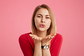 Portrait of positive female wears red sweater and trendy watch, blows kiss as flirts with someone, expresses love and good feelings, isolated over pink background. Glamour woman makes kiss.