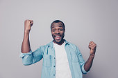 Portrait of positive, happy, shouting, screaming, laughing man with open mouth and raised arms, celebrating successfully completed work, isolated on grey background