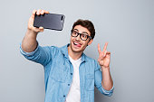 Portrait of positive, comic, trendy guy with stubble shooting selfie on smart phone, using gadget device, gesture v-sign, having video-call, isolated on grey background