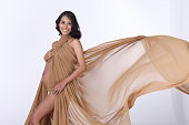 Portrait of Pregnant Asian Indian tanned skin woman brown gold fabric fluttering in Air, Lady with throwing textile waving fashion style, Studio lighting white background