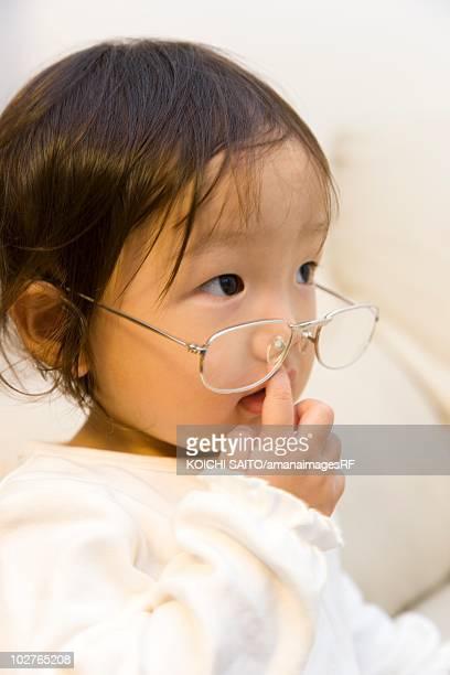 Portrait of preschool age girl wearing her parents glasses