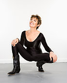 Portrait of pretty Caucasian woman in spandex bodysuit and black cowboy boots smiling.