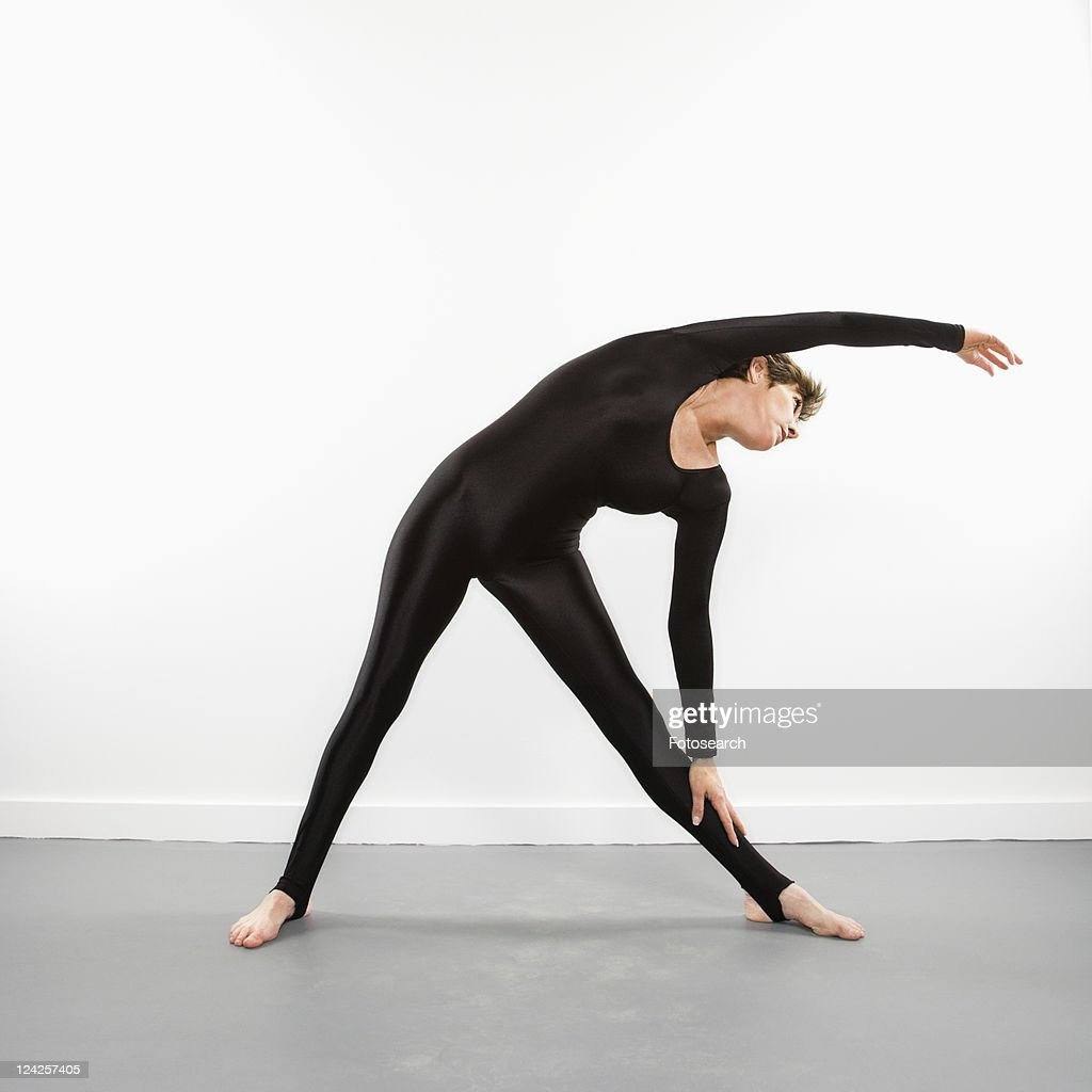Portrait of pretty Caucasian woman in spandex bodysuit leaning and stretching to side.
