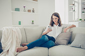 Portrait of pretty, charming, cheerful, trendy house wife in jeans, shirt with curly hair sitting on sofa having cell smart phone in hands chatting with lover searching contact using 3G wi-fi internet
