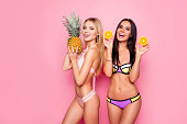 Portrait of pretty, charming, laughing, stylish trendy ladies, tourists with modern hairstyle in swimsuit showing ananas and orange in hands, standing over pink background, brunette vs blonde