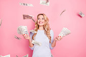 Portrait of pretty charming positive cute successful lucky cheerful girl standing under shower from money having a lot of money in hands isolated on pink background