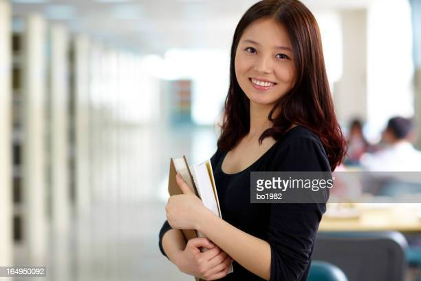 portrait of pretty female college student in library