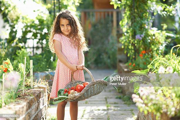 Portrait of pretty girl holding basket of fresh vegetables in garden