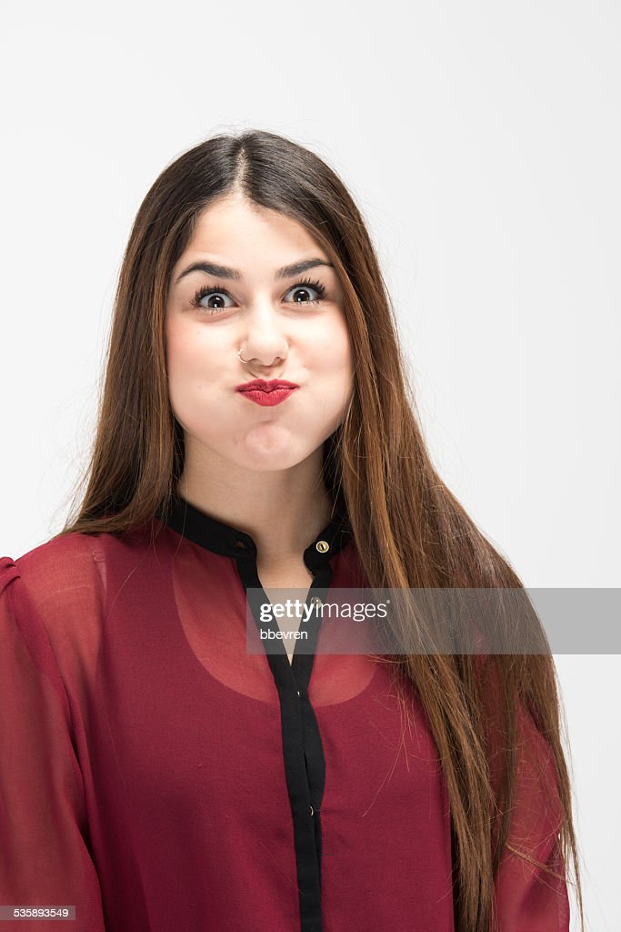 Portrait of pretty girl with puffing cheek gesture : Bildbanksbilder