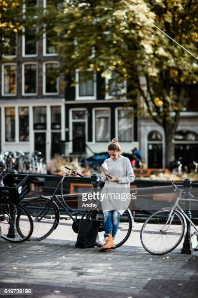 Portrait de jolie femme se penchant sur un vélo, lecture des messages de téléphone