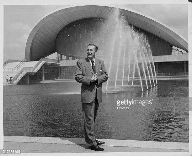 Portrait of producer and animator Walt Disney standing next to a fountain circa 1950
