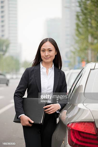Portrait Of Professional Businesswoman Leaning On Car