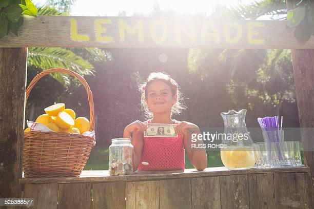 Portrait of proud girl on lemonade stand holding up one dollar bill