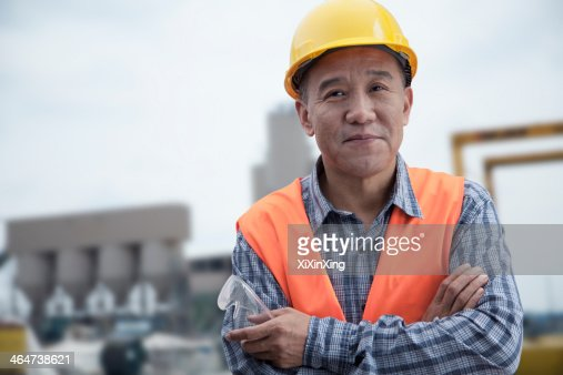 Portrait of proud worker with arms crossed in protective workwear outside of a factory