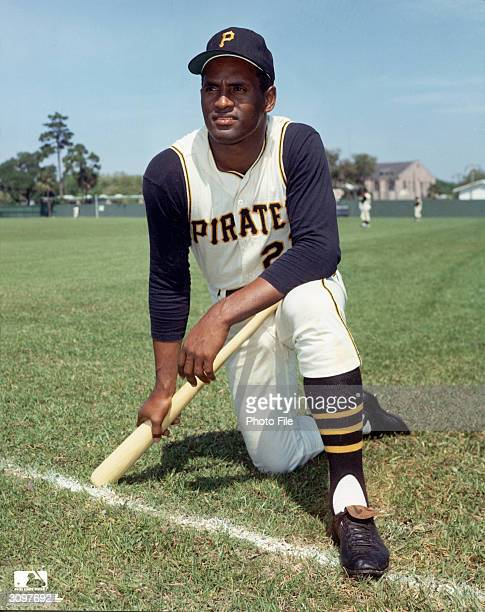 Portrait of Puerto Ricanborn baseball player Roberto Clemente in his Pittsburgh Pirates uniform kneels and holds a baseball bat 1960s