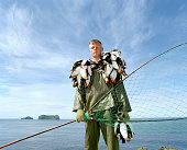 Portrait of puffin hunter Jakob Erlingsson holding the puffins he has caught that day using a net Puffin hunting has been of major importance in...