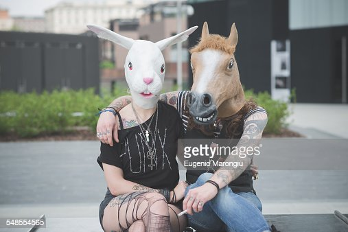 Portrait of punk hippy couple wearing rabbit and horse costume masks