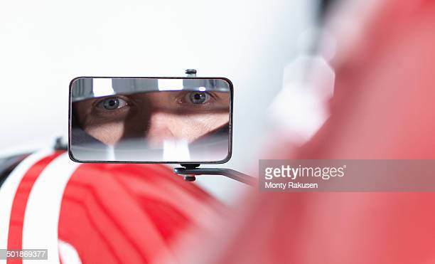 Portrait of racing car driver reflected in wing mirror of supercar