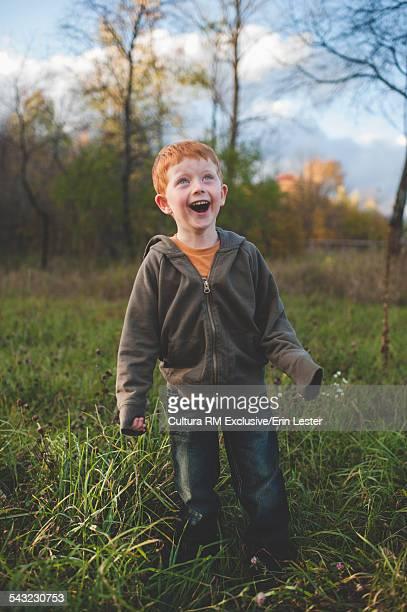 Portrait of red haired mischievous boy in field