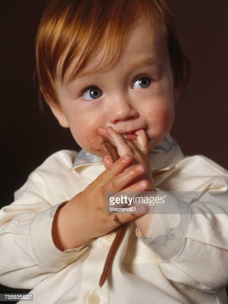 Portrait of redheaded baby boy with toy worm and finger in his mouth