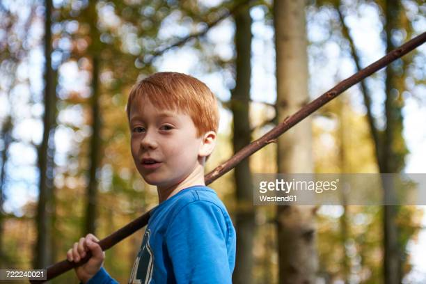 Portrait of redheaded boy with wood stick in the forest