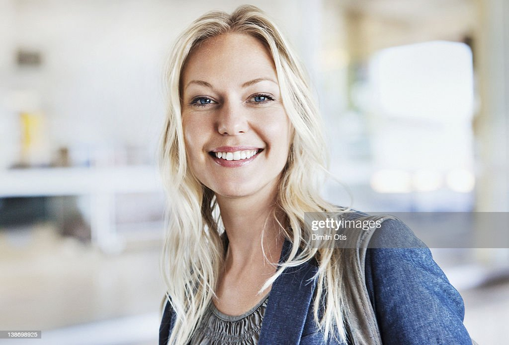 Portrait of relaxed, blonde woman indoors, smiling : Stock Photo