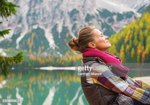 Portrait of relaxed young woman on lake braies, italy : Stock Photo
